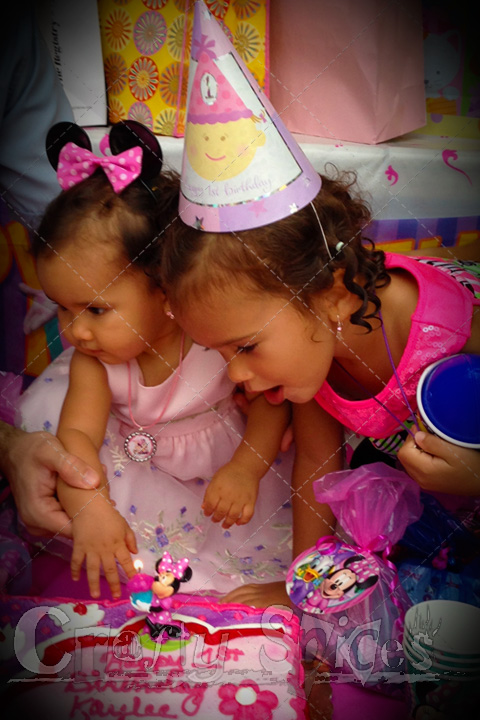 Kaylee blowing the candle and big sister Kira helping her